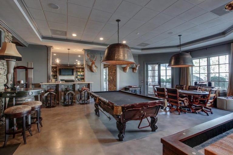 This great room boasts elegant seats and billiards pool along with its lighting hanging from the tray ceiling.