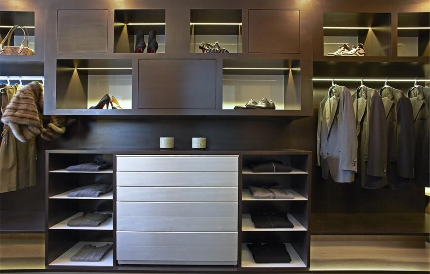 Modern men and women closet featuring brown cabinets and counters. The flooring and lighting of this closet looks elegant.