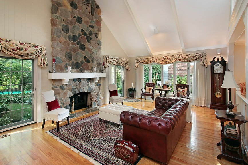 Large formal living room with elegant leather seats along with a stone fireplace. The room features hardwood flooring and a tall ceiling.
