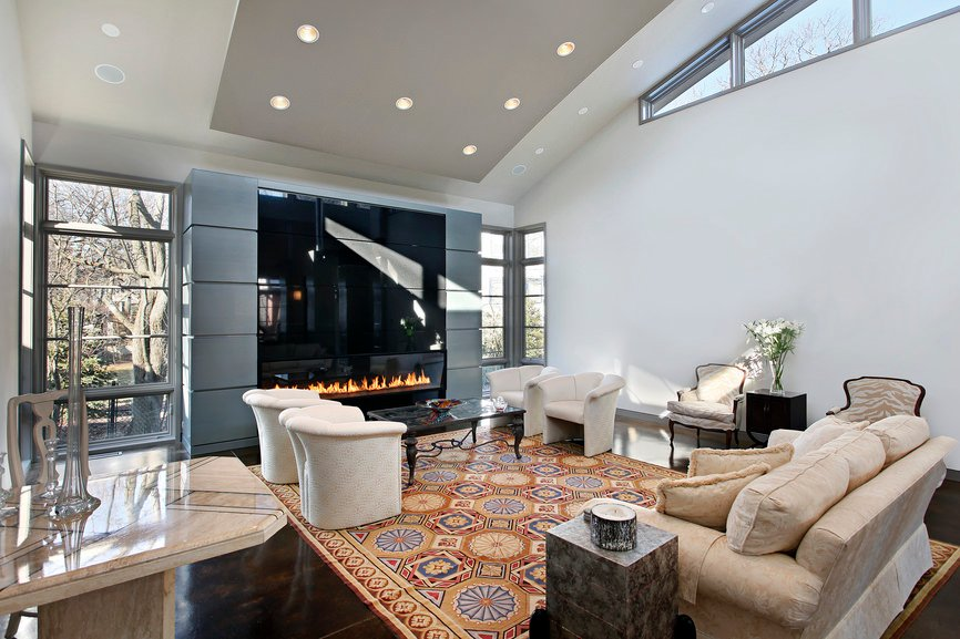 Modern home with a stylish fireplace and ceiling lighted by recessed lights. The rug set on the sparkling tiles flooring looks beautiful as well.