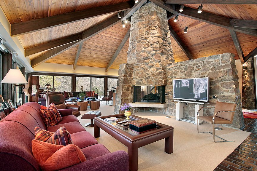A massive formal living room featuring a rustic stone wall and pillar installed with a fireplace. The tall ceiling is just magnificent, perfect together with the home's flooring.