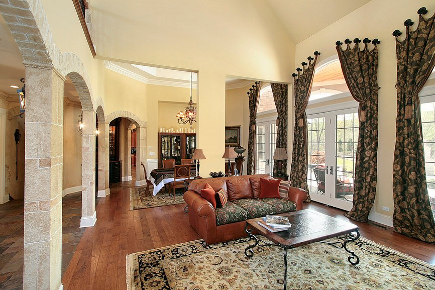 Mediterranean formal living space featuring a brown leather couch and a dining table set behind it. The window curtains, along with the area rugs are all glamorous looking.