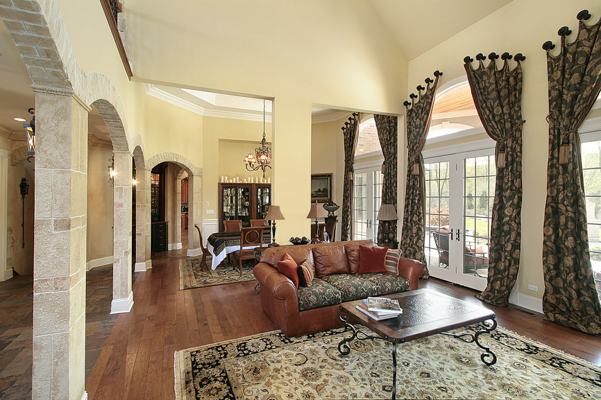 This Mediterranean boasts a lovely pair of window curtains and rugs along with an elegant brown couch.