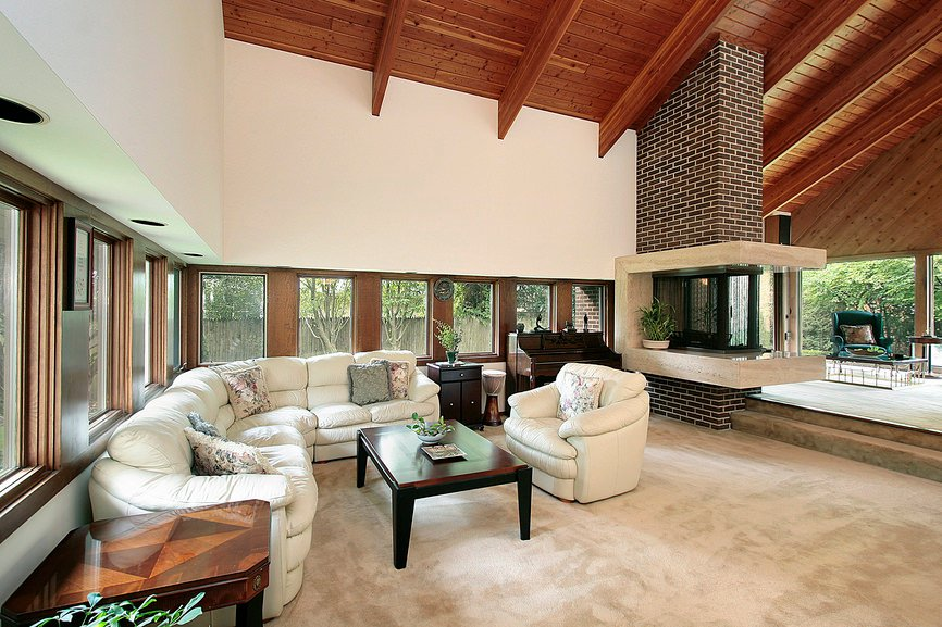 Large formal living room featuring alluring carpet floors. The room boasts wooden tall ceiling.