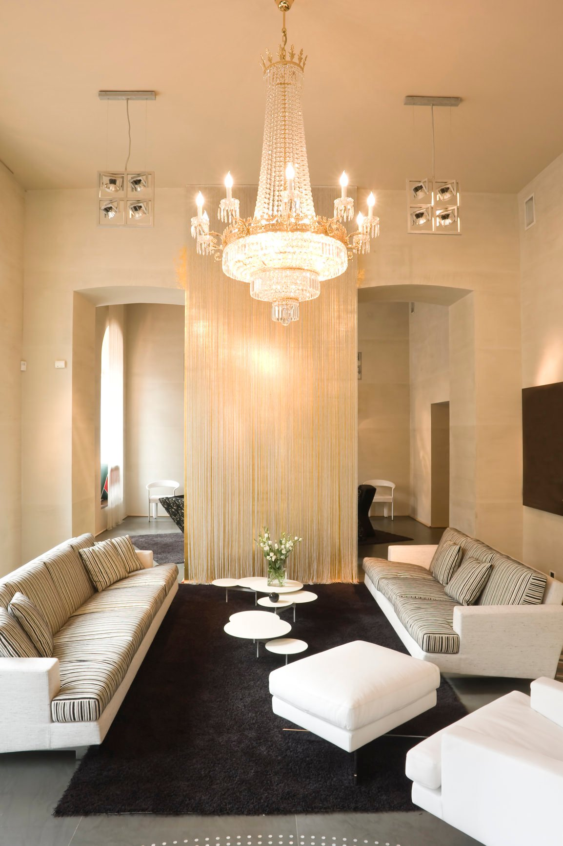 A formal living space featuring an elegant grand chandelier lighting up the space. The room offers a cozy sofa set along with a stylish white center table.