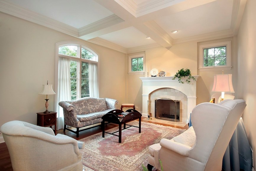 An elegant formal living room with a coffered ceiling with dazzling seats and a charming fireplace.