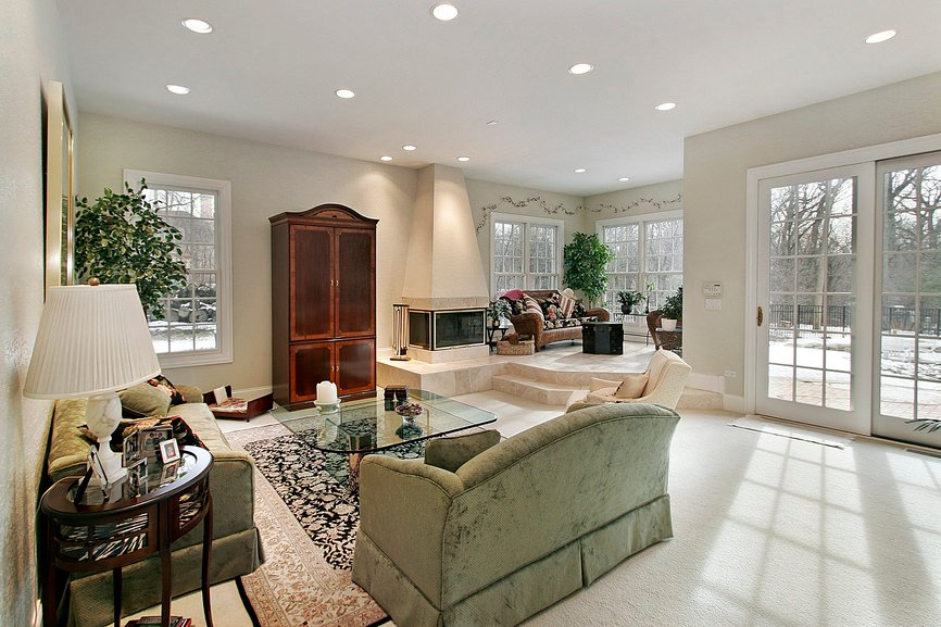 Large living room featuring beige walls and carpet flooring topped by a classy rug. The sofa set looks glamorous together with the other furniture.