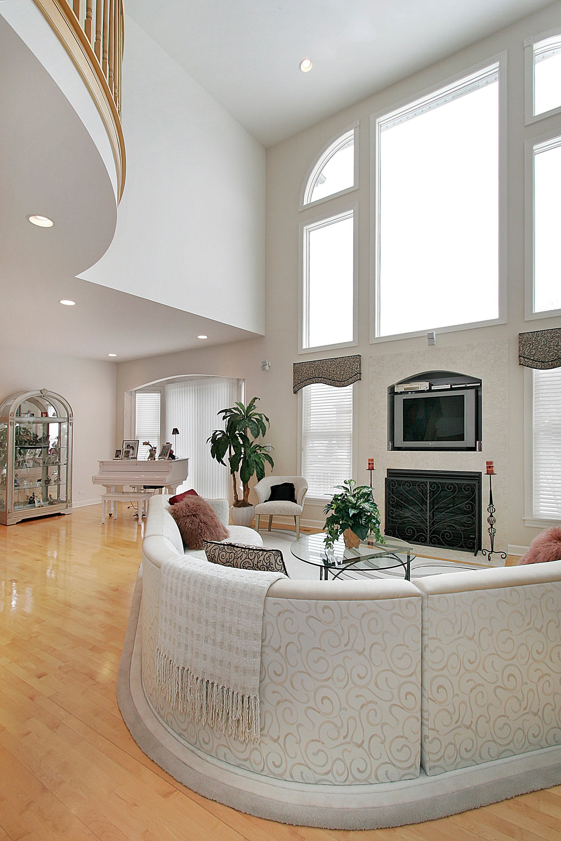 Spacious formal living space featuring an elegant custom sofa set and a fireplace under the tall shed ceiling painted in white.