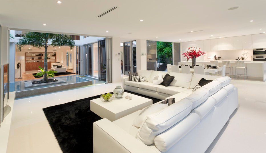 Large open spaced living rooms look even larger with an all white color scheme like shown here.