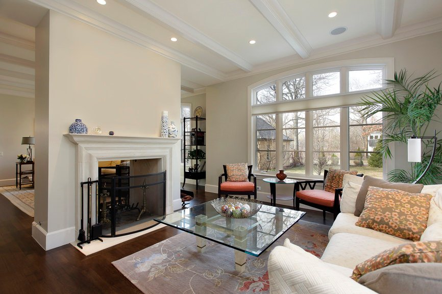 Large living room with classy and comfortable seats with a glass top center table set on the hardwood flooring topped by a rug. The fireplace looks beautiful together with the living room's style.