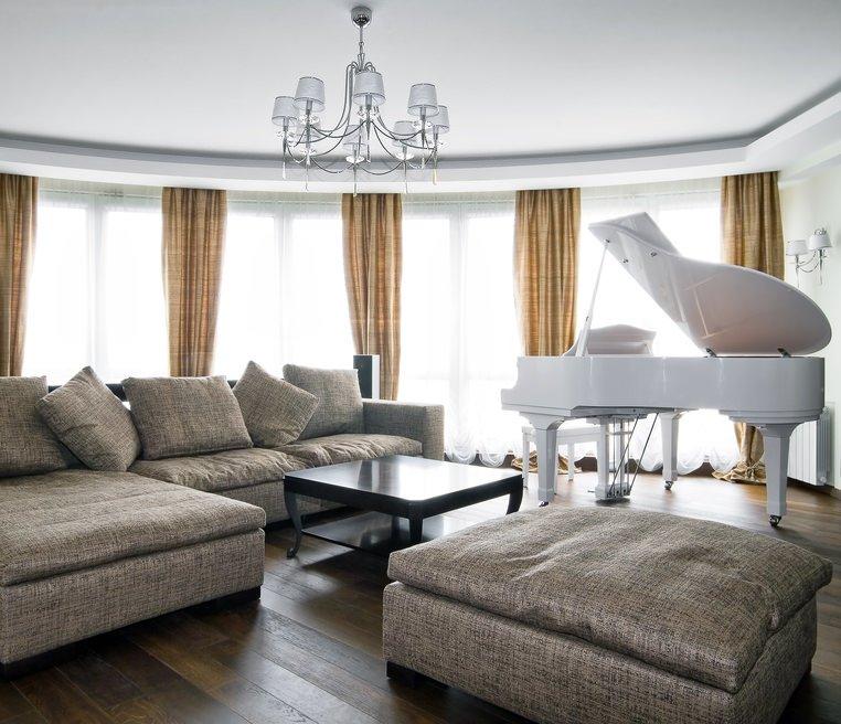 White formal living room with classy window curtains and a cozy sofa set. The white piano on the side looks very charming.