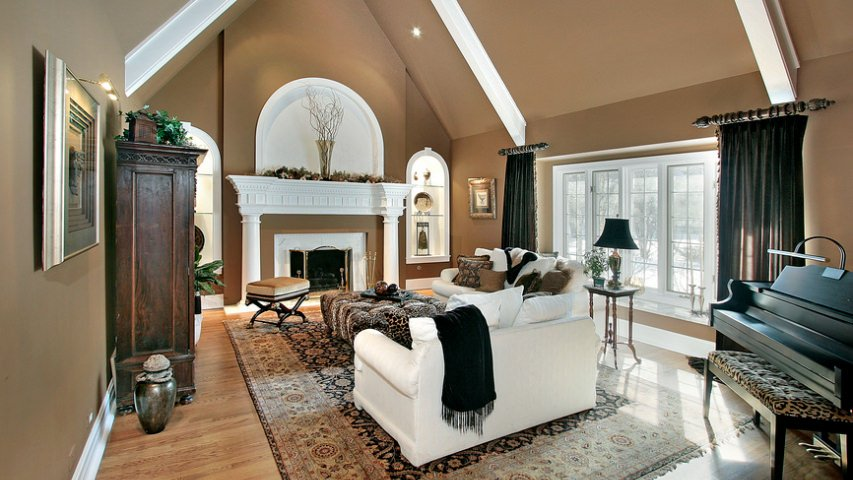 Medium-sized formal living room featuring a tall ceiling with white beams, gray walls and hardwood flooring topped by a large area rug. The room offers a fireplace and a black piano.