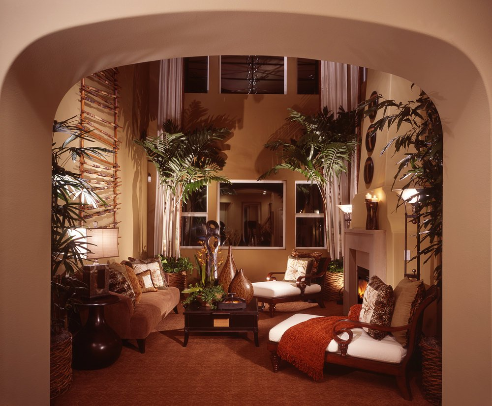 An archway opens to a warm living room with brown velvet sofa and white chaise lounges surrounding a wooden coffee table. It is decorated with wood art pieces and a hanging ladder.