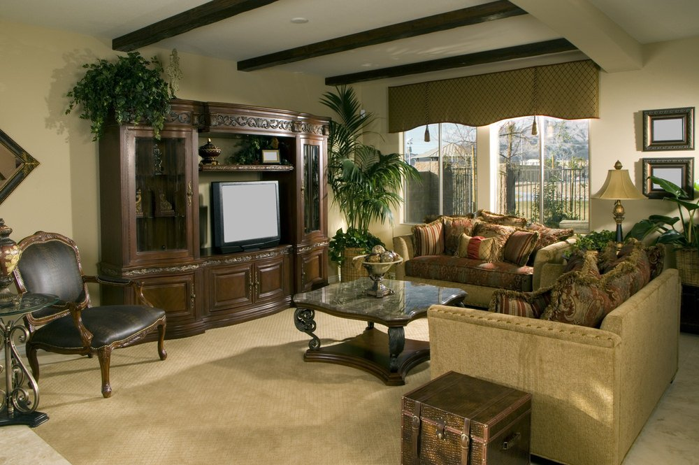 A formal living room featuring carpet flooring and a nice set of seats, along with a regular ceiling with beams.