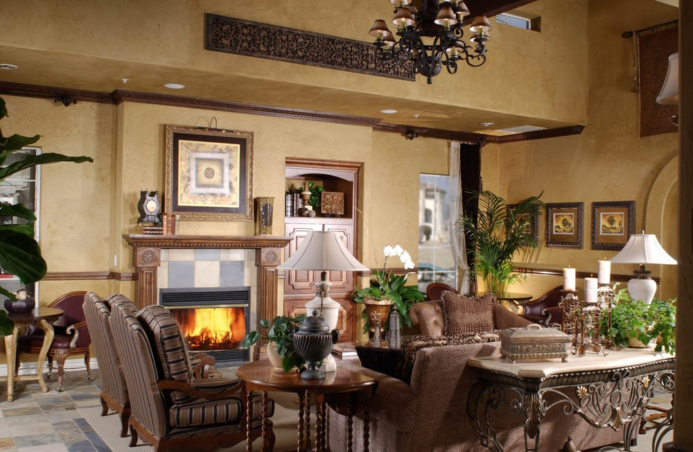 Large Mediterranean living room with a brown set of seats and tables along with a fireplace. The beige walls look absolutely perfect with the kitchen's style.