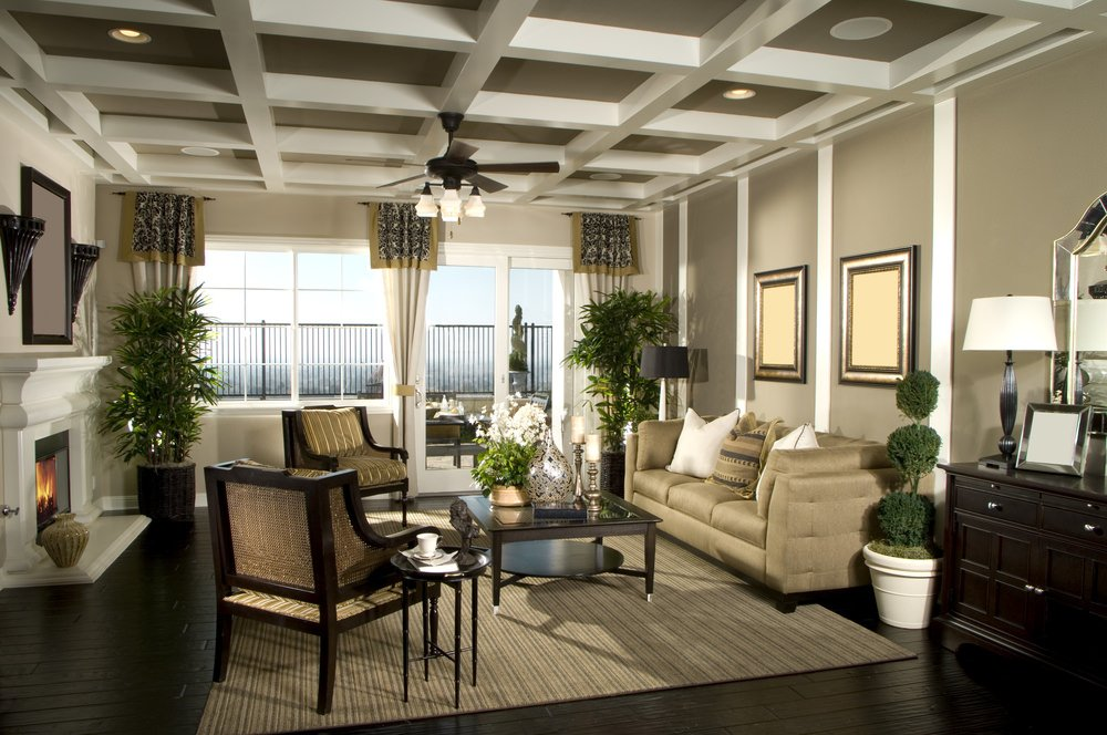 Large formal living room featuring dark hardwood flooring and a coffered ceiling. The room also features a doorway leading to the outdoor areas.