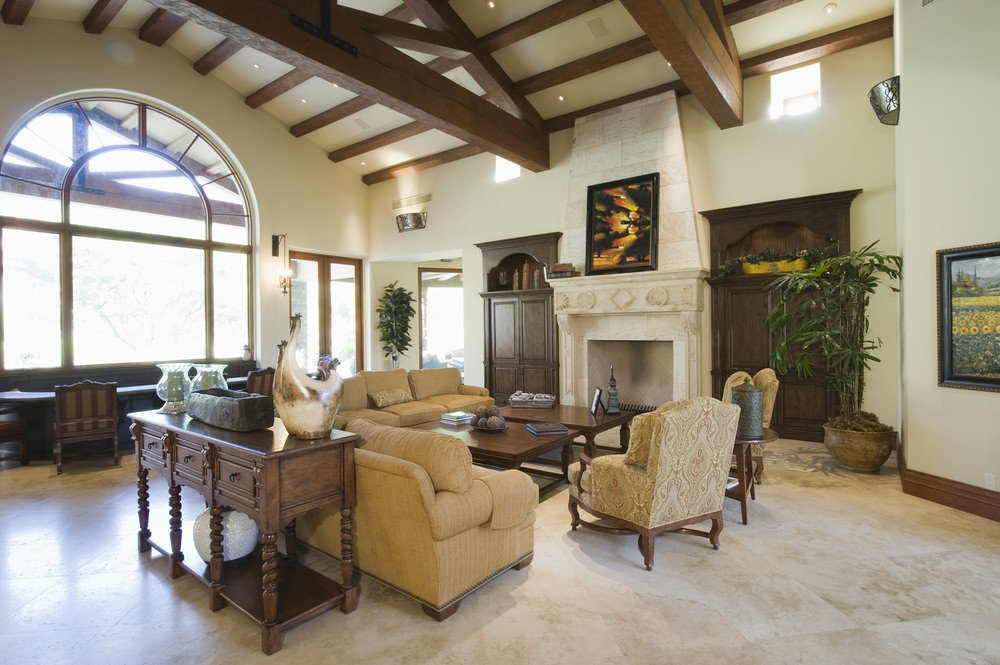 Large Mediterranean living room featuring classy seats and center table near the fireplace.