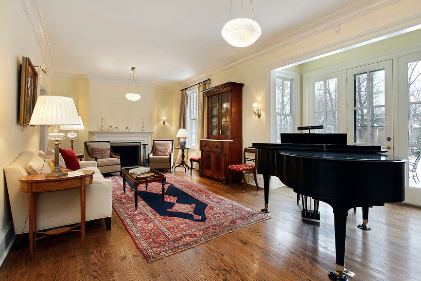 This living room features classy seats and a large fireplace along with a stylish rug covering the hardwood flooring. There's a grand piano as well that looks very elegant.
