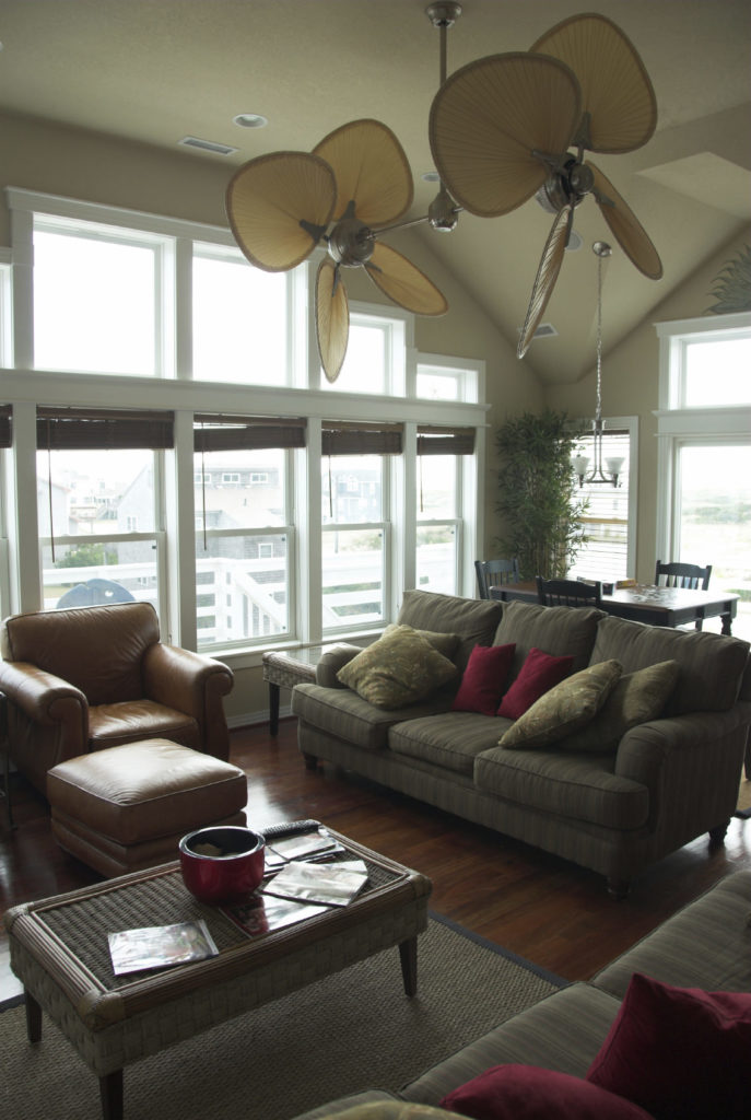 This living room offers comfortable seats set on the hardwood flooring topped by a gray rug.