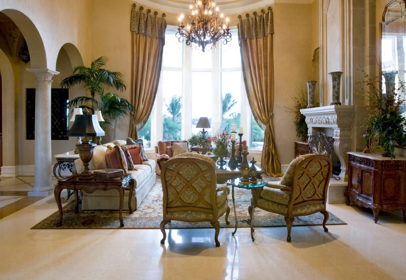 This Mediterranean living room offers a lovely set of seats under the tall ceiling lighted by a glamorous chandelier. The fireplace and the golden window curtains add elegance to this room.