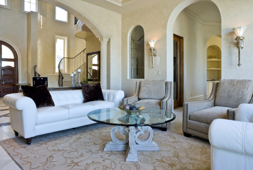 A beautiful Mediterranean living room featuring a nice set of seats with a glass top center table set on the lovely rug. The white walls are lighted by stunning wall lights.
