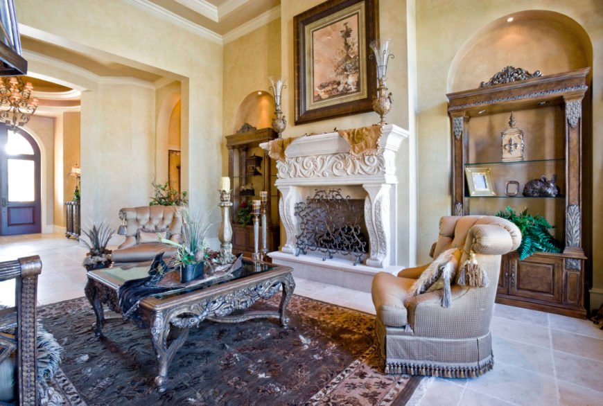 An elegant Mediterranean living room with classy seats and rug along with a stylish fireplace, rustic side cabinets and shelves along with a stunning wall decor.