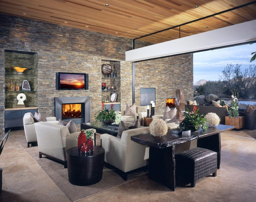 Modern formal living room with stone walls, a cozy living set and a fireplace with a widescreen TV on top.