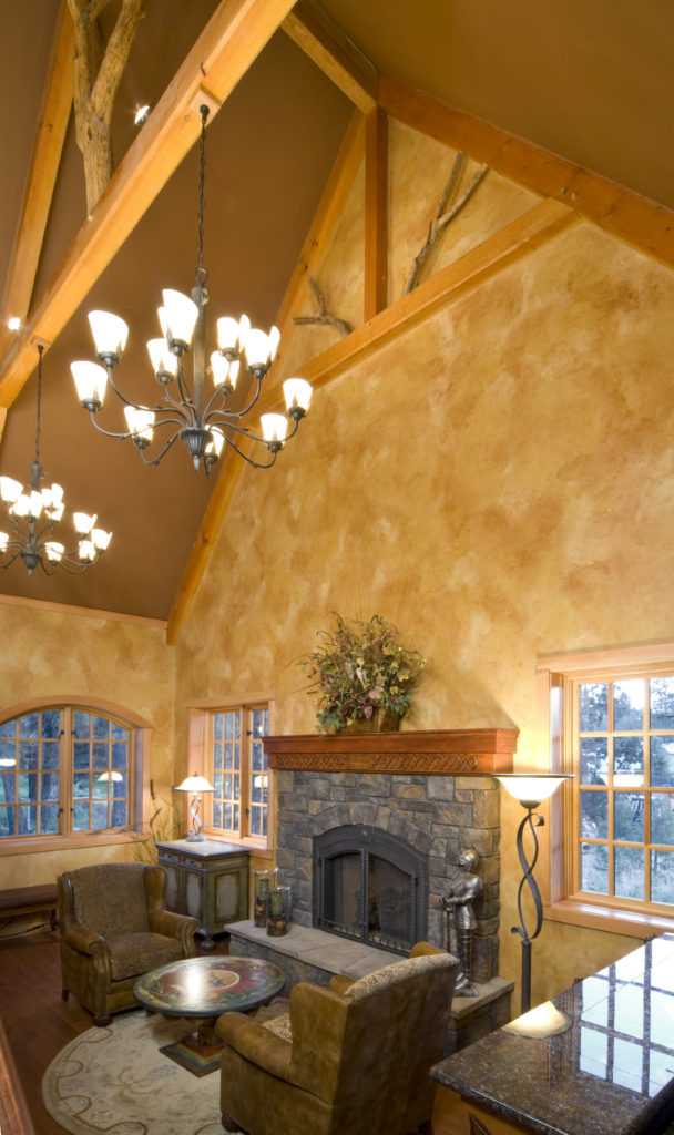This formal living room boasts brown walls and a tall ceiling with exposed beams. The room also offers a fireplace.