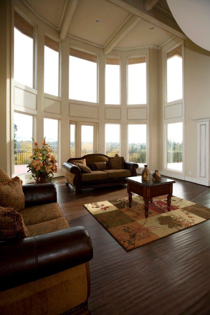 A living room featuring hardwood flooring and a high coffered ceiling.