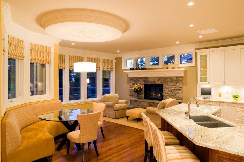 A very beautiful great room with yellow dining nook seats, a classy living space with a fireplace and a lovely kitchen bar.