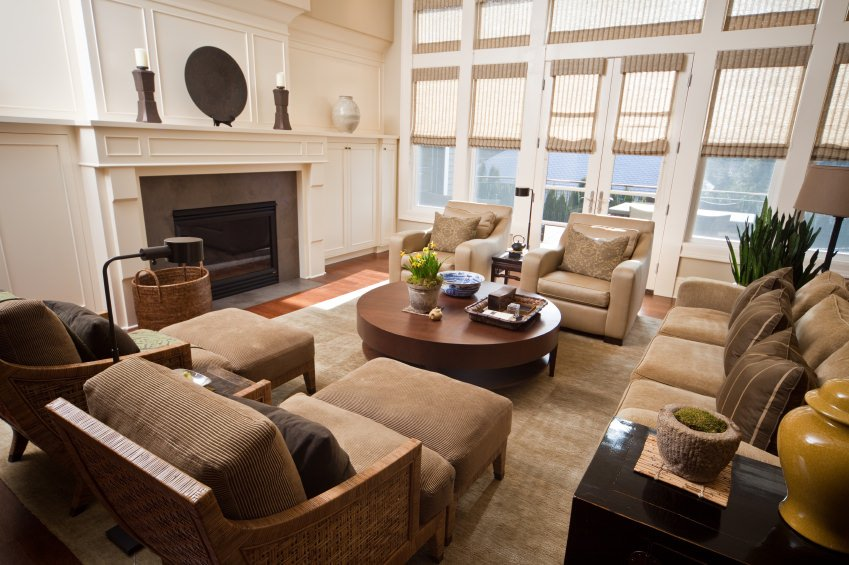This living room offers classy seats along with a stylish round center table set near the fireplace.