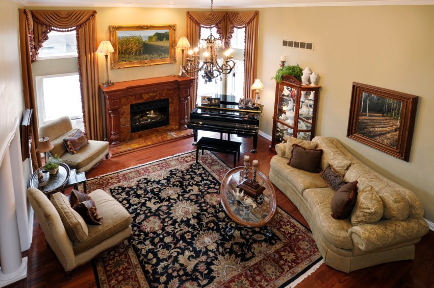 This formal living room offers an elegant fireplace. Near the fireplace is the black piano that looks so stunning. The reddish hardwood flooring is topped by a beautiful rug lighted by a gorgeous chandelier.