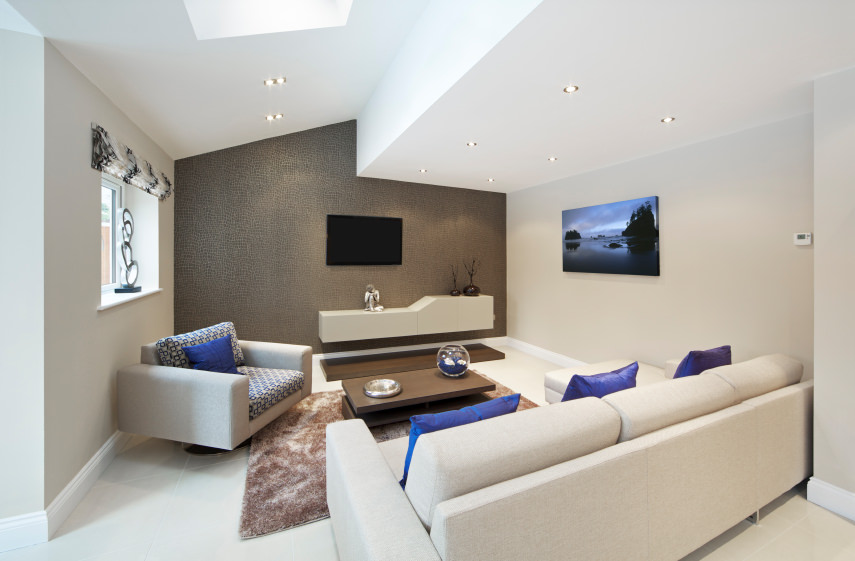 Small formal living room with cozy sofa set and a stylish wall, lighted by scattered recessed lights.