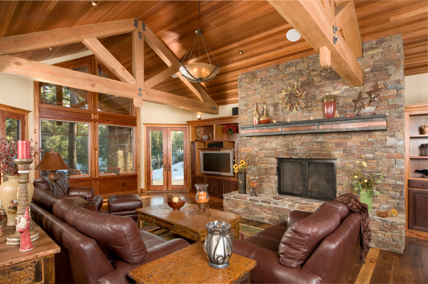 Rustic living room featuring brown leather seats and a large stone fireplace under the home's tall vaulted ceiling with exposed beams.