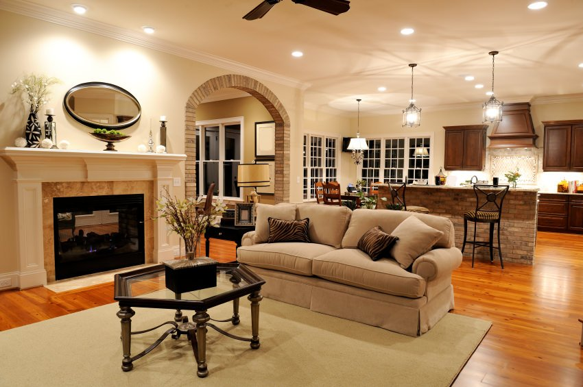 This great room provides a comfortable sofa set near the fireplace along with a stylish kitchen with a bar lighted by pendant lights.