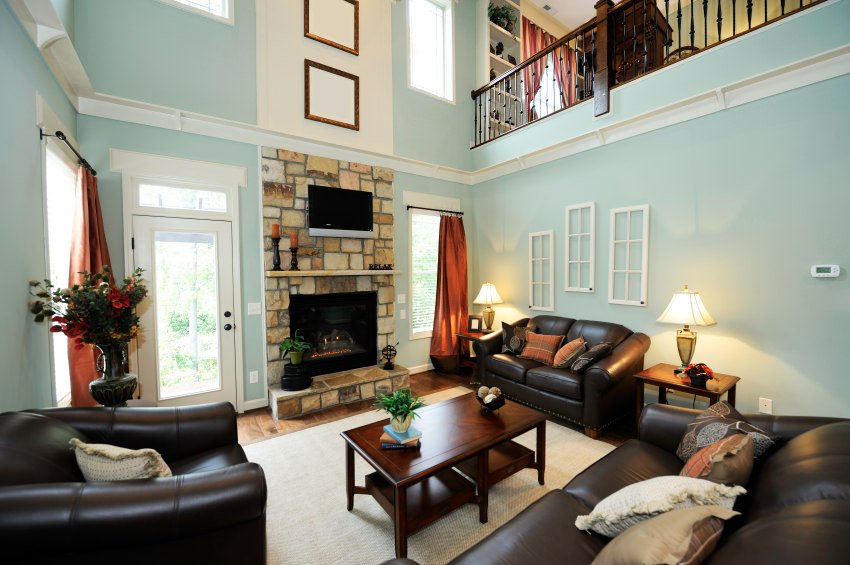 Small living room featuring black leather seats and a stone fireplace, under the two-story ceiling.