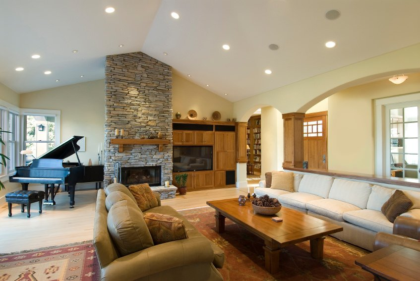 Large living room featuring a widescreen TV, a stone fireplace and a black grand piano in the corner.