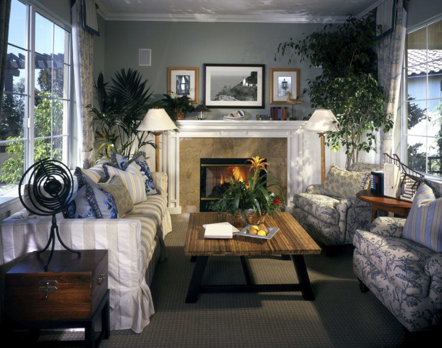 Charming living room with gray walls and carpet flooring. It has a striped skirted sofa filled with lovely blue pillows along with floral armchairs and a wooden coffee table.