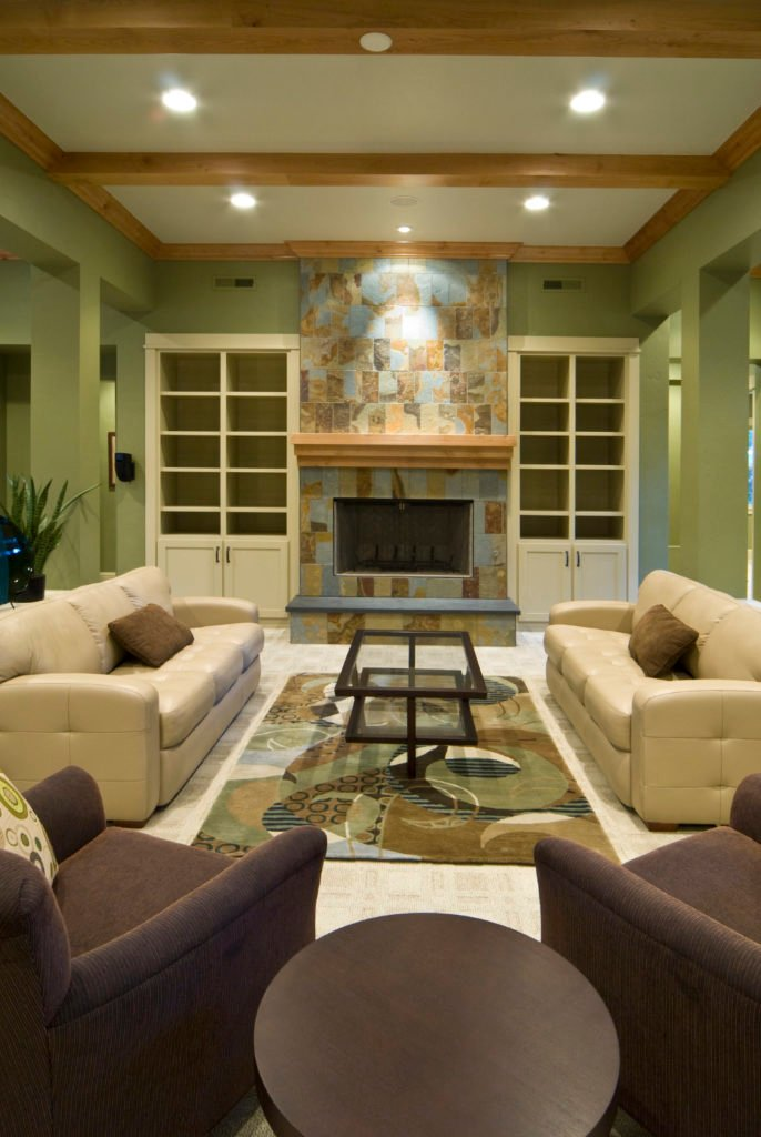 A formal living room with comfy seats and a stylish fireplace that matches well with the area rug.