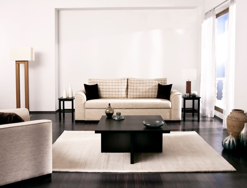 A classy formal living room offering a sleek sofa set and a stylish center table on top of the charming rug set on the hardwood flooring.