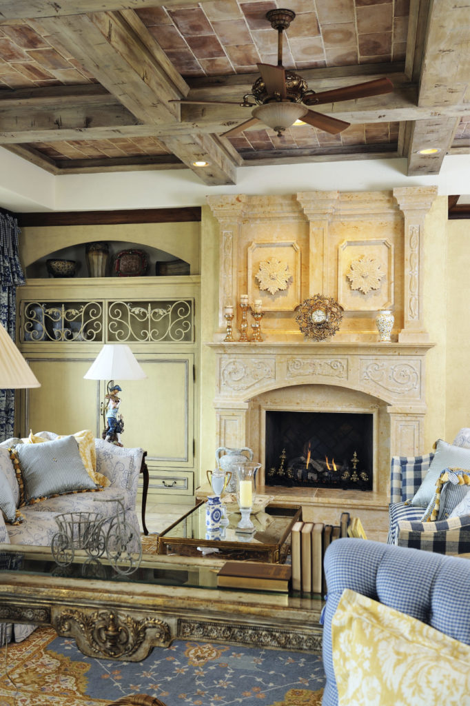 This formal living room offers elegant furniture set along with a large fireplace and a rustic ceiling with beams.