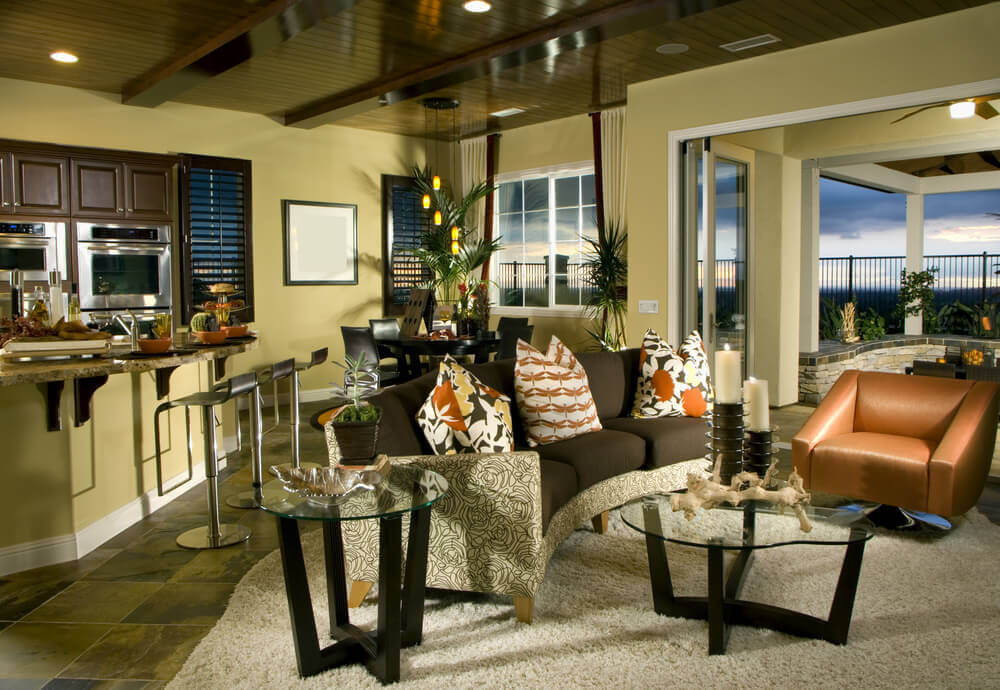 A great room with a nice living set and a breakfast bar along with a round dining nook on the corner.