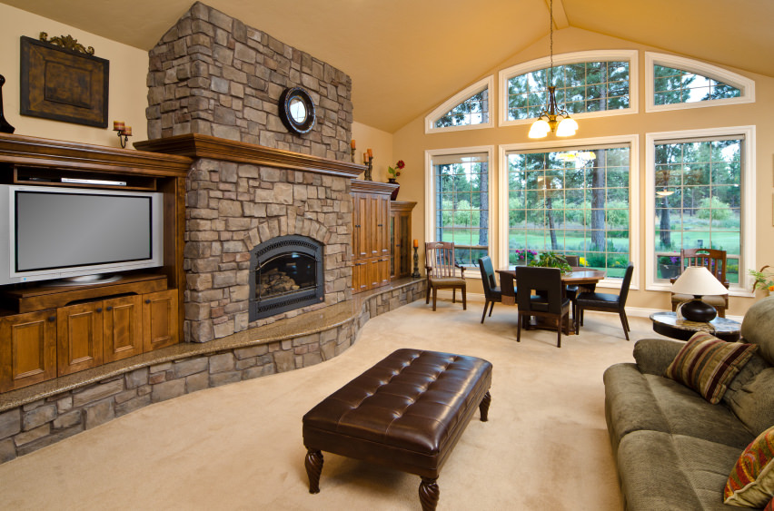 A great room featuring a living space and a dining nook set on the carpet flooring. The area has a fireplace, keeping the space warm.