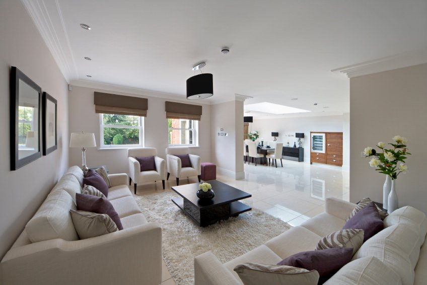 This living room features white couches and chairs together with the rug and sparkling tiles flooring.