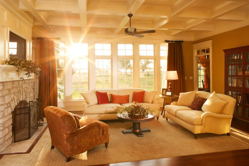 Warm afternoon sunlight pours into an elegant homes living room with a stone fireplace and large windows looking out into the yard.