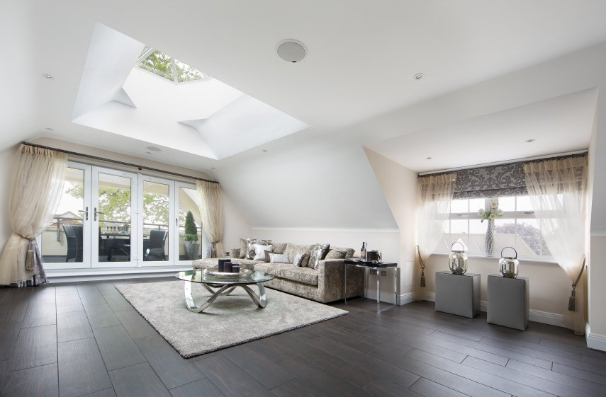 A spacious formal living room featuring an elegant couch set on the hardwood flooring topped by a classy rug. The ceiling offers a stunning skylight.