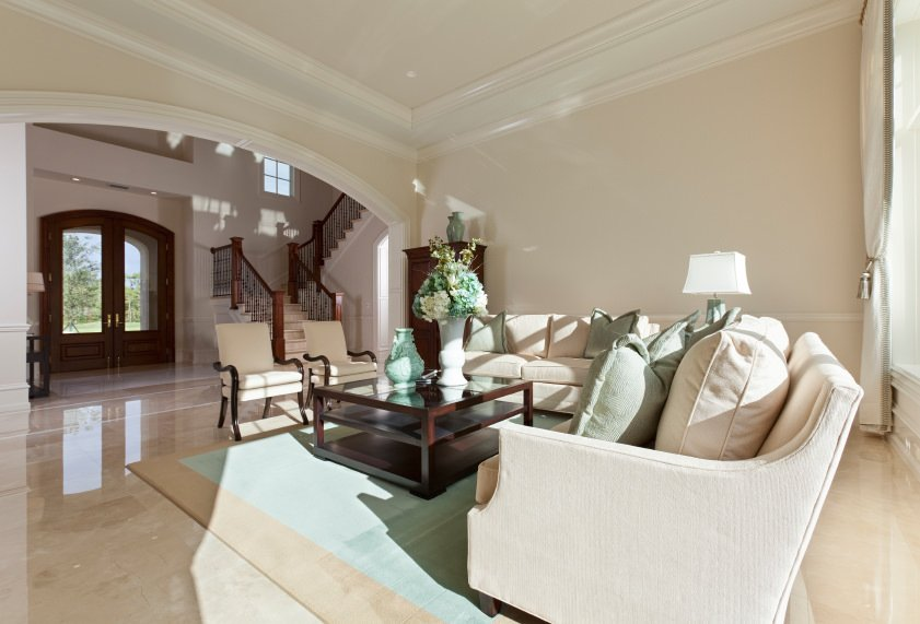Large living room with classy seats and tiles flooring topped by a rug.