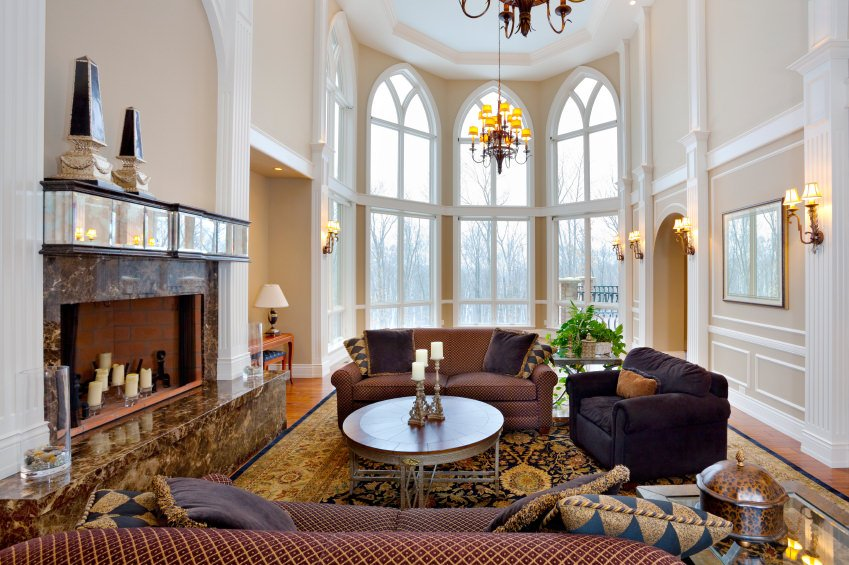 Large living room with soaring ceiling, chandelier, arched windows, wall sconces, and a marble fireplace.