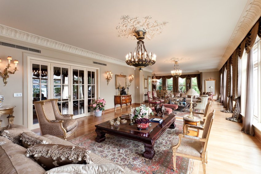 Large living room with gorgeous furniture and chandelier sets. The wall lighting looks absolutely glamorous as well.