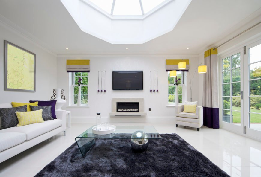 This white formal living room offers a stylish fireplace and a ceiling with skylight. The sofa set looks perfect together with the white flooring.